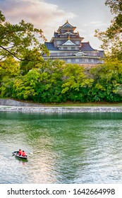 Okayama Crow Castle or Ujo Castle in Okayama City on the Asahi River in Japan. With Little Boat In Foreground. Vertical image Composition