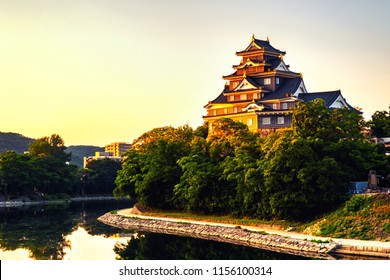 Okayama, Japan. Castle in Okayama, Japan in the morning with river and colorful yellow sky at sunrise. Reflection in the water