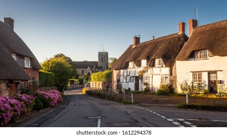Okeford Fitzpaine, England, UK - August 26, 2012: Traditional timbered and thatched cottages line a street in the village of Okeford Fitzpaine in the Blackmore Vale neighbourhood of Dorset.