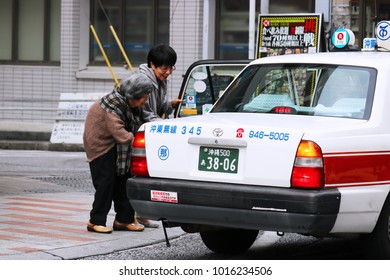 Okinawa, JP - JANUARY 31, 2018: A friendly good female taking an old lady into the white taxi.