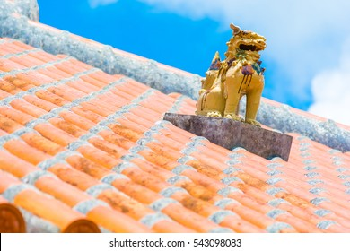 Okinawa Ryukyu style roof with a sculpture of Shasa mythical lion dog with blue cloudy sky in Okinawa island, Japan