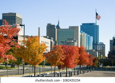 Oklahoma city skyline in fall foliage with flying American flag