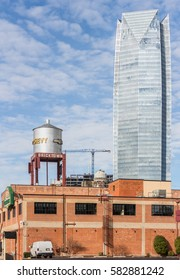 Oklahoma City, Oklahoma, USA - Jan. 25, 2017: Old red brick building, Chevy water tower, Devon Energy Center corporate office skyscraper in background. Examples of vintage and modern architecture.