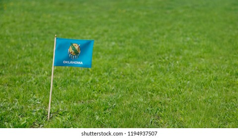Oklahoma flag. Photo of Oklahoma state flag on a green grass lawn background. Close up of state flag waving outdoors.