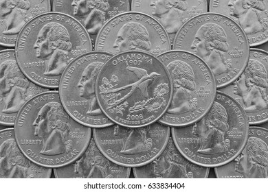 Oklahoma State and coins of USA. Pile of the US quarter coins with George Washington and on the top a quarter of Oklahoma State.