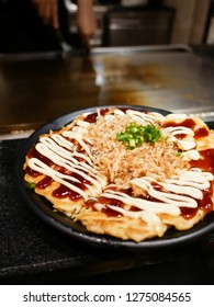 Okonomiyaki (Japanese pancake with cabbage and made to order ingredient) served in front of hot iron griddle. One of the most popular menu in Teppan yaki restaurant