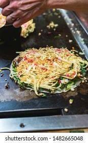 Okonomiyaki, Japanese pancake in the making. Tasty traditional dish from Hiroshima prefecture, Japan.