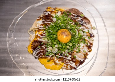 Okonomiyaki, a Japanese pizza / pancake containing a variety of ingredients, on the pan.