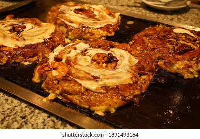 Okonomiyaki, Japanese style savory pancake made with flour, eggs, shredded cabbage, meat and topped with a variety of condiments