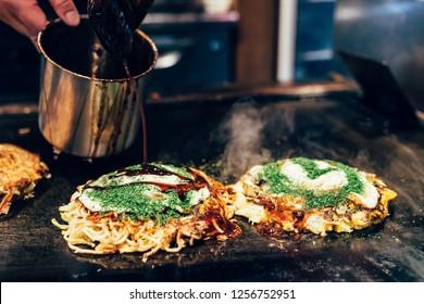 Okonomiyaki on teppanyaki pan. chef pour the salty sauce on japanese style pancake to make it delicious. hot traditional street food on the iron plate.
