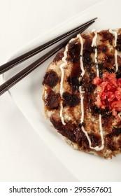 Okonomiyaki on white plate with chopsticks.
