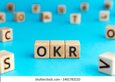OKR - acronym from wooden blocks with letters, Objectives and Key Results OKR concept, random letters around, white  background
