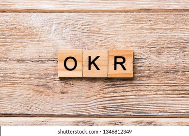 OKR word written on wood block. abbreviation of Objective Key Results text on wooden table for your desing, concept.