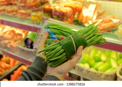 Okra bundled in a plastic package and beans wrapped in Banana leaf held in female hands. This is an excellent solution how replace plastic packaging and reduce the waist of it - Bali, Indonesia