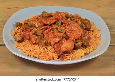 Okra cooked with tomatoes, sausage, ingredients and seasonings served over Mexican style cooked white long rice in gray porcelain dish over wooden kitchen table