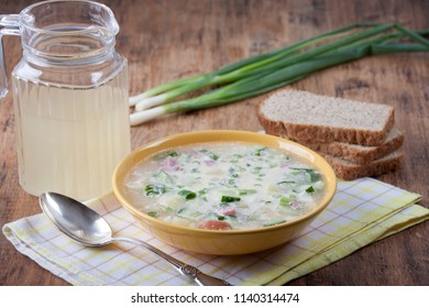 Okroshka on kvass in a yellow plate and a jug of kvass on a wooden table