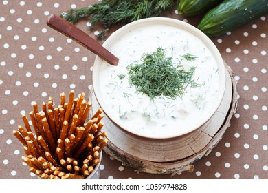 Okroshka on yogurt. Traditional cold soup made of cucumbers, onions, dill, with yoghurt filling. Top view.