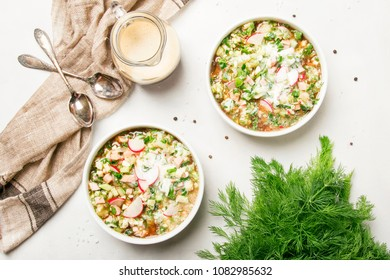 Okroshka - Traditional Russian cold summer soup with vegetables, meat and herbs, dressed with bread kvass and kefir, white background, top view