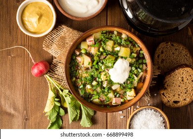 Okroshka. Traditional Russian summer cold soup with sausage, vegetables and kvass in bowl on wooden background. Top view.