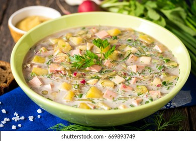 Okroshka. Traditional Russian summer cold soup with sausage, vegetables and kvass in bowl on wooden background. Selective focus.