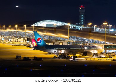 Oksaka, Japan. December 5, 2018. Korean Air Lines Boeing 777-200 Reg. HL7721 Parking at Gate Terminal with Long Jet Bridge for Boarding Passenger at Kansai International Airport at Night. Copy Space