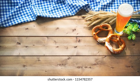 Oktoberfest background with Bavarian flag, beer glass and pretzel on rustic wooden table