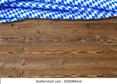 Oktoberfest background frame with bavarian white and blue fabric on wooden board.  October fest bavarian template.