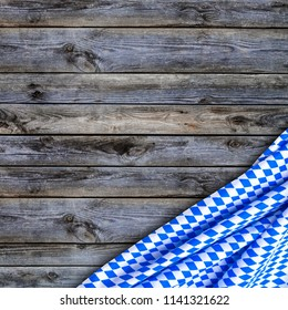 Oktoberfest background  frame  with bavarian white and blue fabric on grey wooden board. October fest background, flat lay, copy space