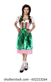 Oktoberfest! Beautiful young brunette woman with pigtails in a traditional Bavarian costume looking at camera standing on white background