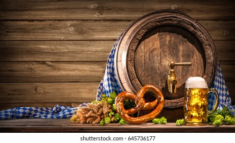 Oktoberfest beer barrel and beer glass with wheat and hops on wooden table