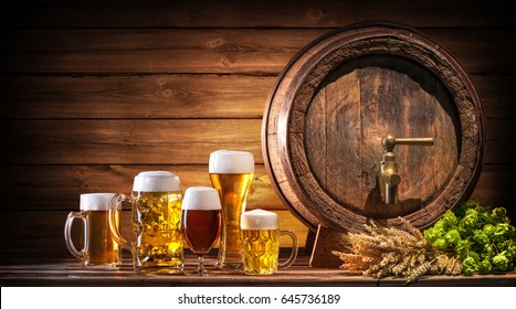 Oktoberfest beer barrel and beer glasses with wheat and hops on wooden table
