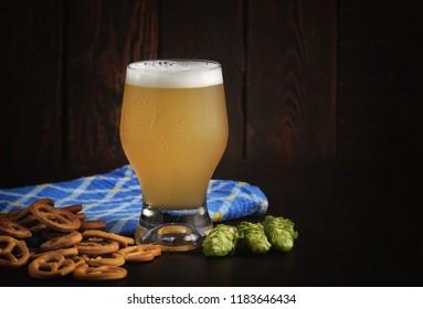Oktoberfest beer festival concept. Cold lager beer in glass on dark wood background