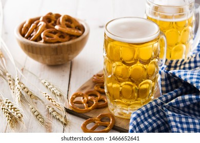 Oktoberfest beer and pretzel on white wooden table.