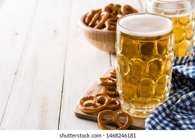 Oktoberfest beer and pretzel on white wooden table.Copyspace