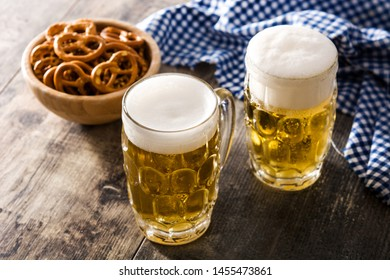 Oktoberfest beer and pretzel on wooden table.