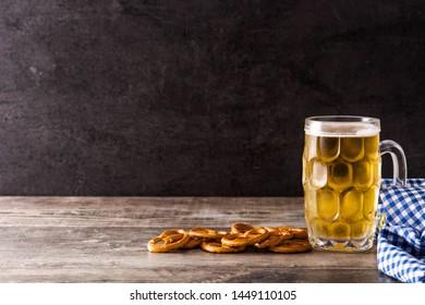 Oktoberfest beer with pretzels on wooden table. Copyspace
