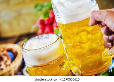 Oktoberfest beer, pretzels and various Bavarian specialties on wooden background