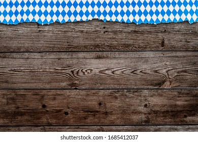Oktoberfest border with bavarian white blue torn paper on horisontal wooden rustic table, copy space, text place, flat lay.  October fest runner background