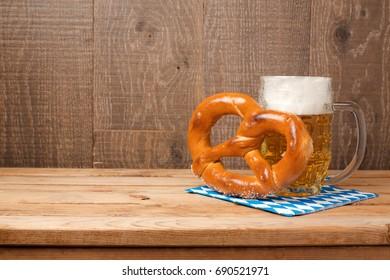 Oktoberfest celebration concept with beer mug and pretzel on wooden background