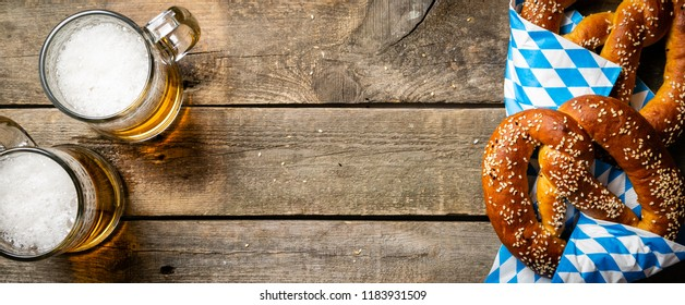 Oktoberfest concept - pretzels and beer on rustic wood background, top view