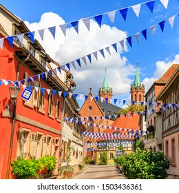 Oktoberfest decoration in old street of  German town. Old frame houses in german medieval city. Street with traditional Houses and  October fest garland. German Oktoberfest card