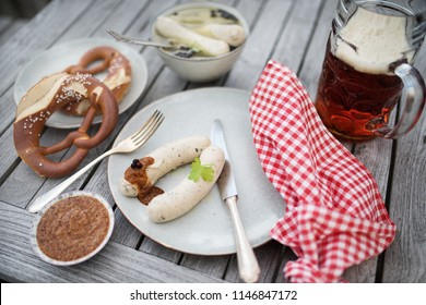 Oktoberfest food bavarian white sausage in a beer garden on wooden table