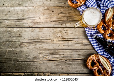 Oktoberfest food menu, bavarian pretzels with beer bottle mug on old rustic wooden background, copy space above