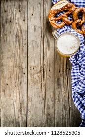 Oktoberfest food menu, bavarian pretzels with beer mug, old rustic wooden background, copy space above