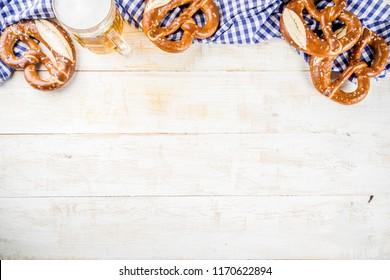 Oktoberfest food menu, bavarian pretzels with beer bottle mug, white wooden background copy space top view