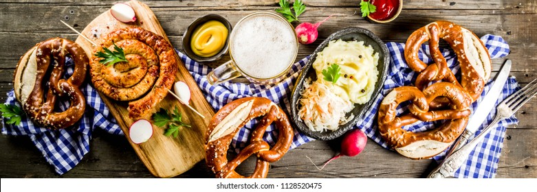Oktoberfest food menu, bavarian sausages with pretzels, mashed potato, sauerkraut, beer bottle and mug old rustic wooden background, copy space above banner format