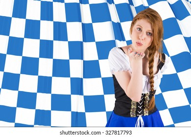 Oktoberfest girl blowing a kiss against blue and white flag