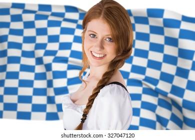 Oktoberfest girl smiling at camera against blue and white flag