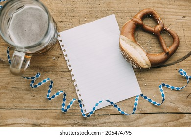 Oktoberfest: Masskrug of beer, Pretzels and bavarian streamer on rustic wooden table with empty piece of paper