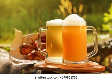 Oktoberfest mug beer with traditional festival food on tree background.